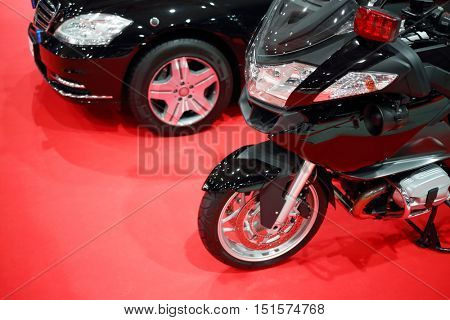 Black shiny bike for cortege, car are on red carpet in exhibition hall