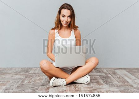 Portrait of a smiling woman sitting on the floor with laptop computer isolated on gray background