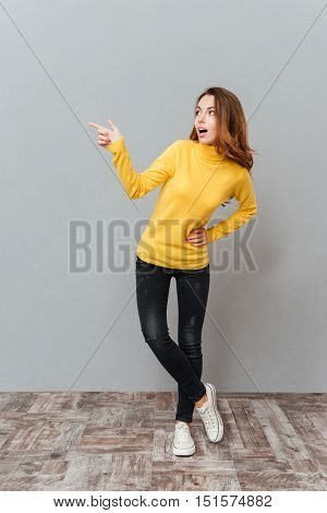 Cheerful excited young woman in yellow sweater standing and pointing away over gray background