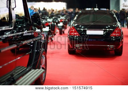 Black shiny cars are on red carpet in hall at auto exhibition