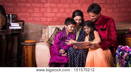 Smiling Indian family on the sofa using technology or tablet or tab or mobile, Indian family shopping online on diwali / taking selfie using tablet or mobile, people celebrating diwali with technology