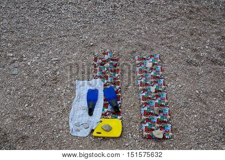Beach gear flippers with sporty kickboard on towels and mats on empty pebble stone shore on summer day