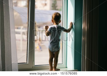 Cute baby boy kid child with blond hair in striped romper stays on sill and looks at window at home