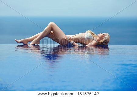 Beautiful Sexy Woman Enjoying, Blond Model Tanned And Lying On Border Of Infinity Swimming Pool Over