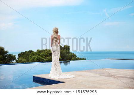 Beautiful Bride Wedding Portrait. Elegant Blond Woman With Long Wavy Hair Wearing In White Fashion M