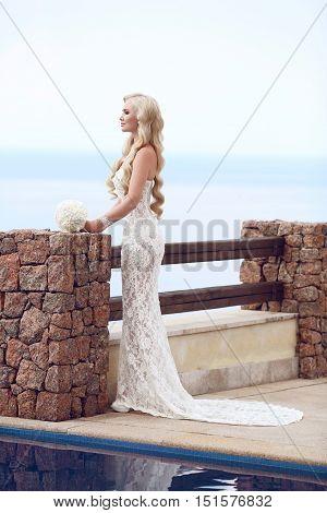 Beautiful Bride Portrait Holding Wedding Bouquet Posing In Formal Prom Lace Mermaid Dress. Wavy Hair