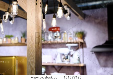 Incandescent light bulbs in a loft style room interior with furniture