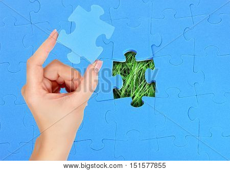 Female hand with missing puzzle piece. Blue pazzle over green grass background.