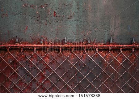 old red metal rusty fence with notched on gray worn wall background