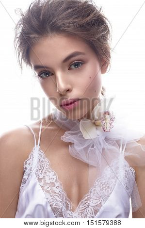 Beautiful girl in image of bride with flower orchid on her neck. Model with nude makeup and silk underwear. Beauty face. Photo was taken in a studio.