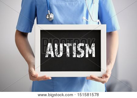 Children autism concept. Female doctor with blackboard, closeup