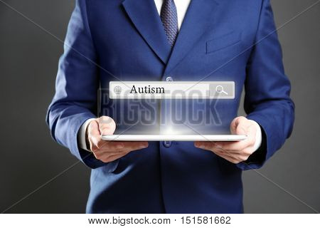 Businessman with tablet on grey background. Children autism concept