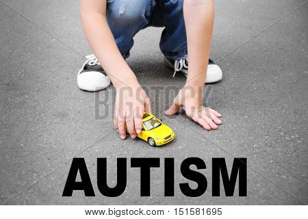 Children autism concept. Little boy playing with toy car outdoor