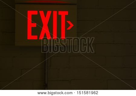 red emergency exit sign in the dark room. illuminated office exit sign. empty space for your text