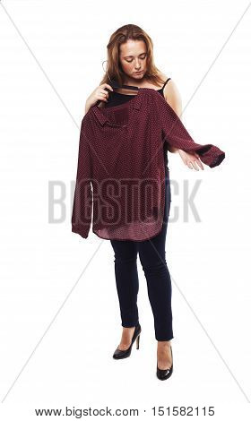 woman holding blouse isolated on white background. young girl chooses clothes. trying on outfits. the concept of fashion. in full growth