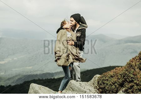 Handsome man hipster kisses pretty girl outdoors on stone cliff on mountain scene