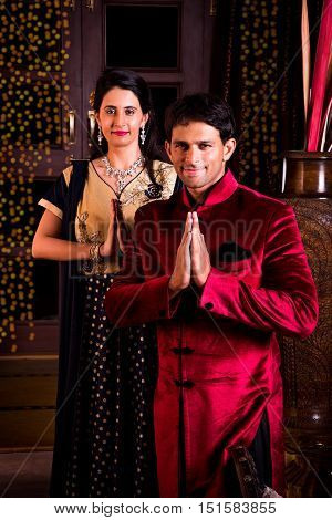 cheerful indian young couple welcoming on diwali night inside home with diwali lighting, indian couple or people in namaskar pose welcoming guests on diwali celebration or festival night