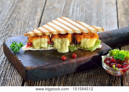 Toasted panini triangles with breaded mini camembert cheese loaves, cranberries and iceberg lettuce served on a wooden cutting board