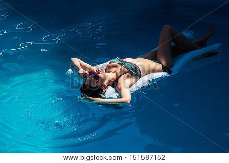 Young girl with beautiful sexy body in bikini laying on air mattress and having sunbath on summertime vacation on blue water background of pool