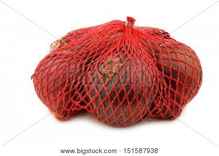 red onions in a red plastic net on a white background