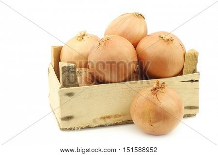 big brown onions in a wooden crate on a white background