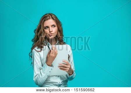 The thoughtful young business woman with pen and tablet for notes on a blue background