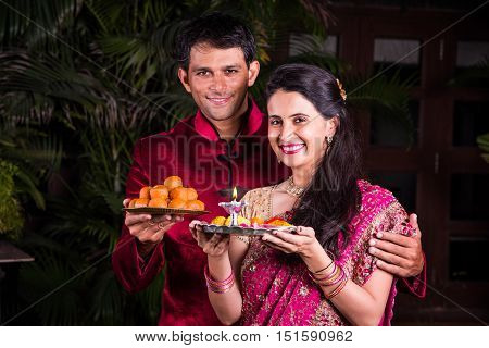 smart looking indian young Husband and wife in traditional wear holding a plate full of motichoor laddu or bundi laddu and puja thali respectively, couple holding puja thali and sweets on diwali