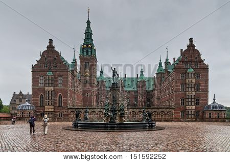 Hillerod Denmark - August 06 2010: Tourists visiting the Frederiksborg palace and the baroque gardens in rainy weather. The palace dates back to the 16th century and now houses The Museum of National History in Hillerod Denmark on August 06 2010.