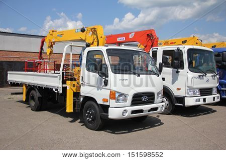 White Flatbed Trucks With Crane Arm Is In The Parking Lot - Russia, Moscow, 30 August 2016