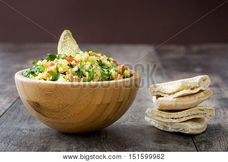 Tabbouleh salad with couscous on rustic table