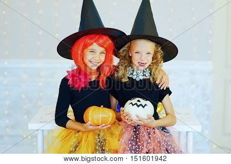 Two little girls in witch costume during Halloween party playing around the table with pumpkins and bottle of potion