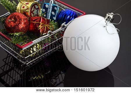 Christmas tree decorations in the shopping cart on a black background