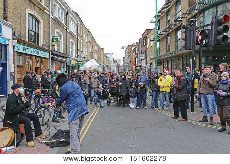 LONDON UNITED KINGDOM - NOVEMBER 24: Street Performance at Brick Lane in East London on NOVEMBER 24 2013. Buskers With Audience at Busy Brick Lane on Sunday in London United Kingdom.