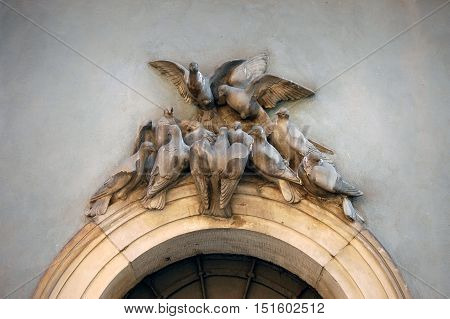 WARSAW, POLAND - JUNE 11, 2010: A fragment of the old facade with sculptures of pigeons above the entrance. Warsaw, Poland.