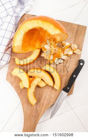 into slices cut hokkaido pumpkin and kitchen knife on wooden board
