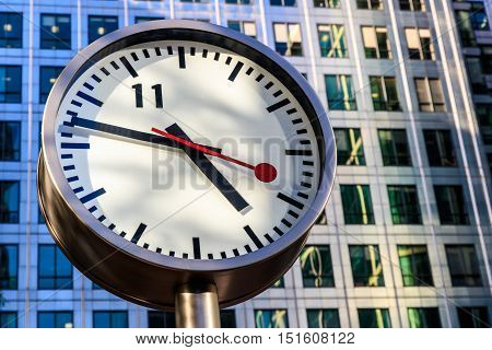 Public clock in Canary Wharf London against office building