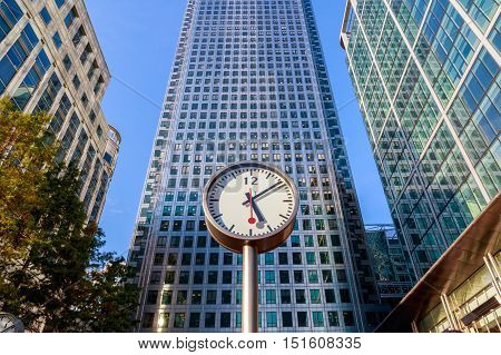 Clock and skyscrapers in Canary Wharf financial district of London