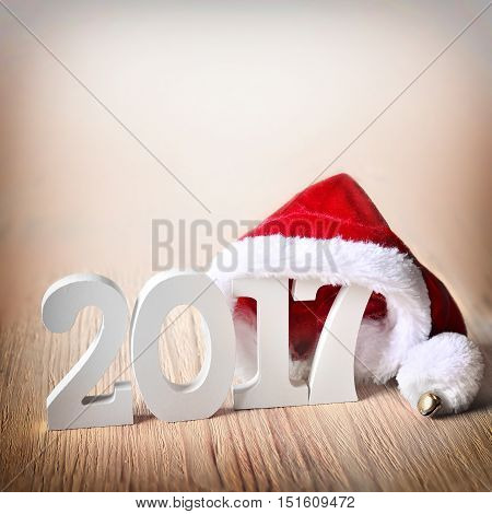 santa fur cap on a rustic wooden background with figures 2017