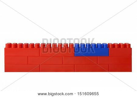Red wall from blocks of the children's designer. One block on green is replaced.