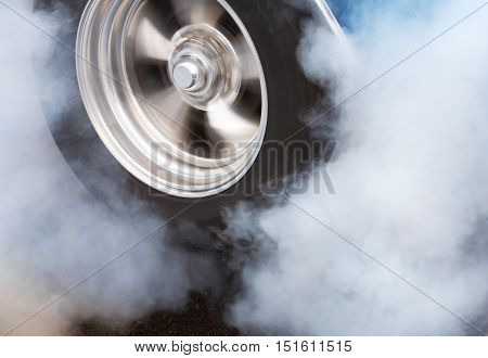 A car doing a burnout so that the tires spin smoke and smell of rubber.