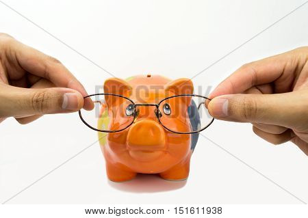 hands putting the glasses to the piggybank like concept of saving in the buy of glasses