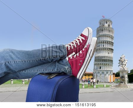 relaxed person with feet above the suitcase on arrival in Pisa