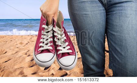 woman holding a shoe in hand and relaxed on the beach