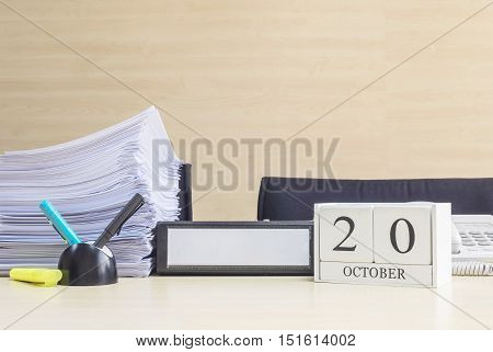 Closeup white wooden calendar with black 20 october word on blurred brown wood desk and wood wall textured background in office room view with copy space selective focus at the calendar