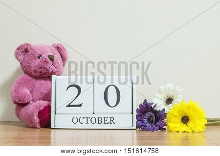 Closeup surface white wooden calendar with black 20 october word on brown wood desk and cream color wallpaper in room textured background with copy space selective focus at the calendar