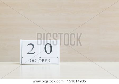 Closeup surface white wooden calendar with black 20 october word on blurred brown wood desk and wood wall textured background with copy space selective focus at the calendar