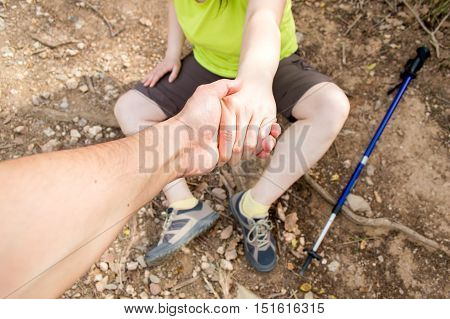 detail of man helping with his hand to lift the woman fell in accident at the mountain