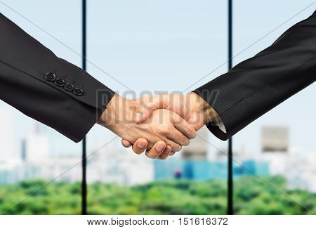 business handshake between partners with city skyline through the window on the background