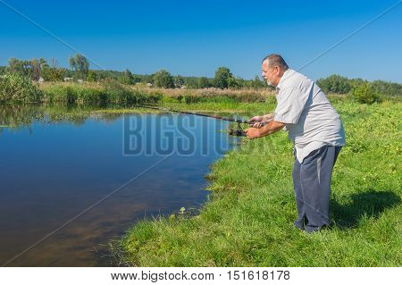 Excited senior fisherman standing on a riverside with spinning rod and ready to catch fish in small river Merla central Ukraine