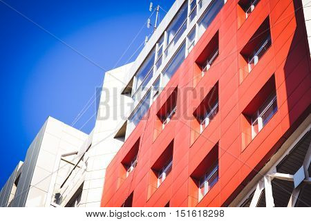 facade, front of the large house red and gray in the high-tech style on a bright sunny day on blue sky background